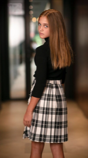 preteen model in sweater and plaid skirt