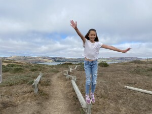 Natalia posing in front of a beautiful view of Bodega Bay that looks like a painting