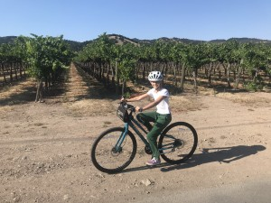 Natalia biking in front of grape vines
